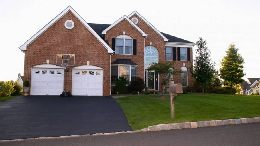 suburban home with red brick and asphalt driveway