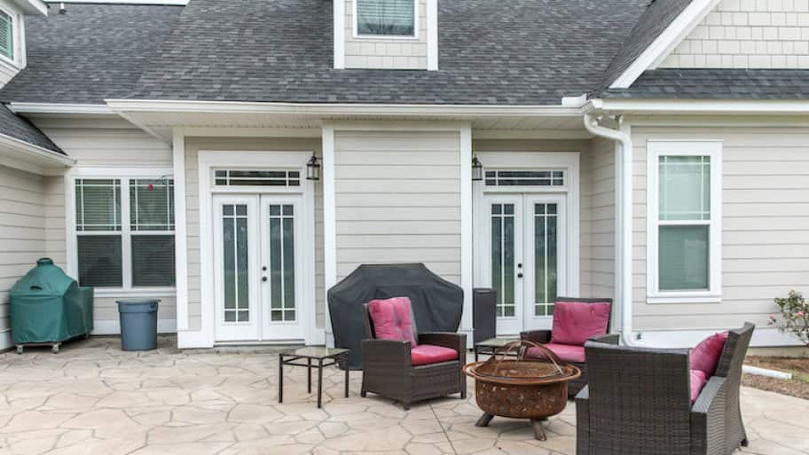 The back rear view of a new construction home with a covered up barbecue and patio furniture with a stamped concrete patio floor