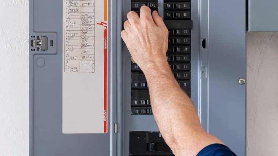 Technician turning power off (Photo by The Toidi/ Shutterstock.com)
