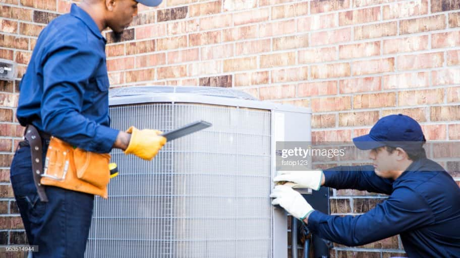 Two technicians repairing a HVAC system
