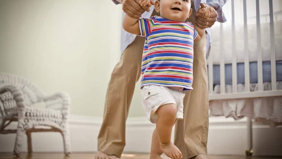 Toddler being helped across hardwood floor