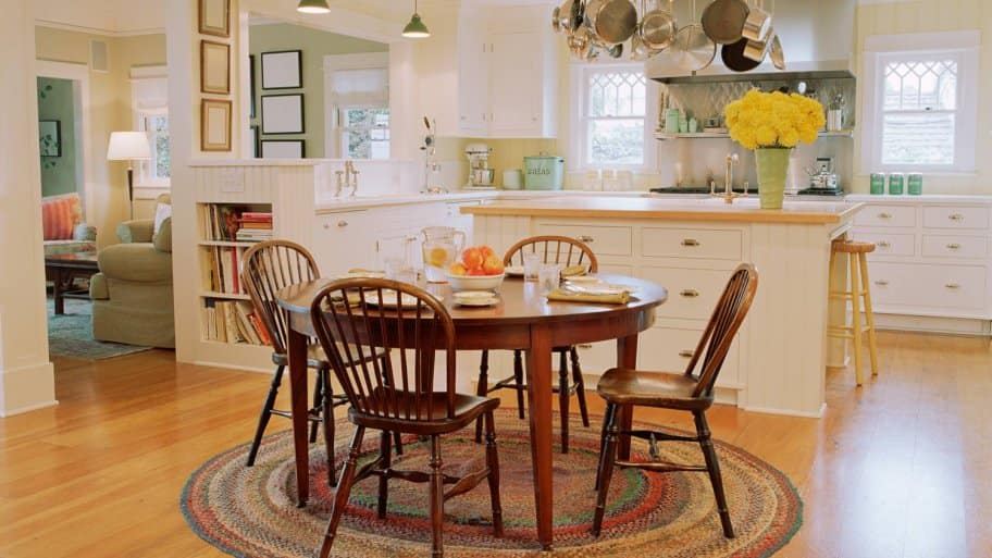 A traditional kitchen with wooden table, chairs and hardwood floor