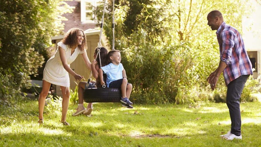 Parents Pushing Children On Tire Swing