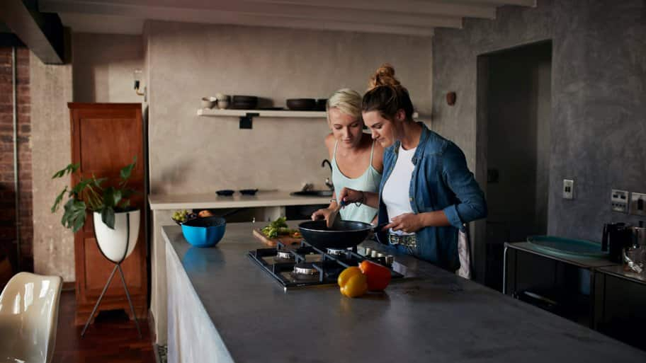 Two young women cooking on a kitchen island
