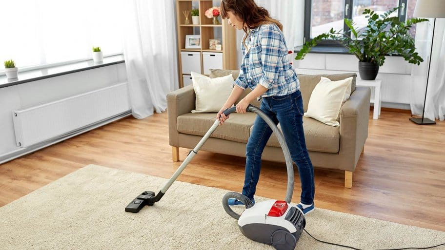 Woman with vacuum cleaner in living room