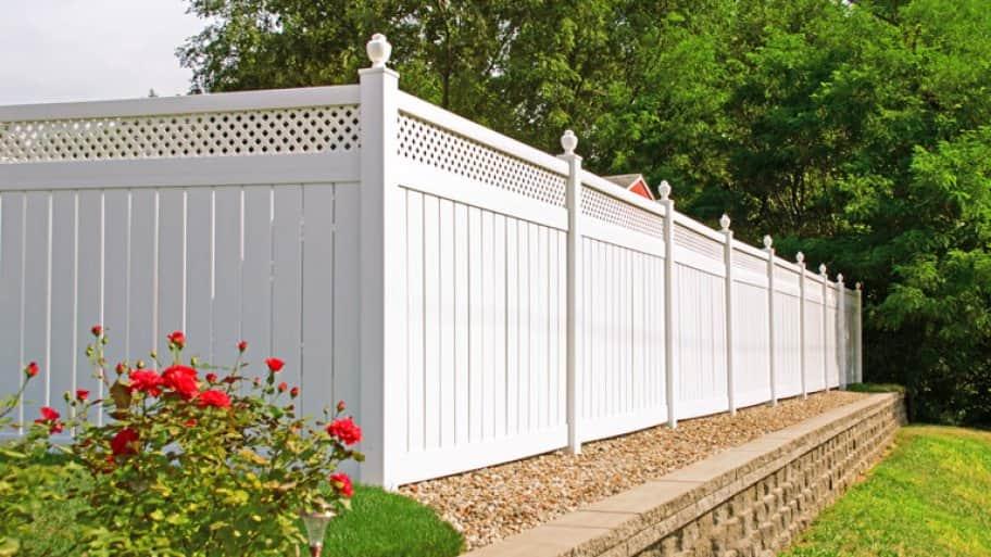White vinyl fence in backyard with nice landscaping in the foreground and background