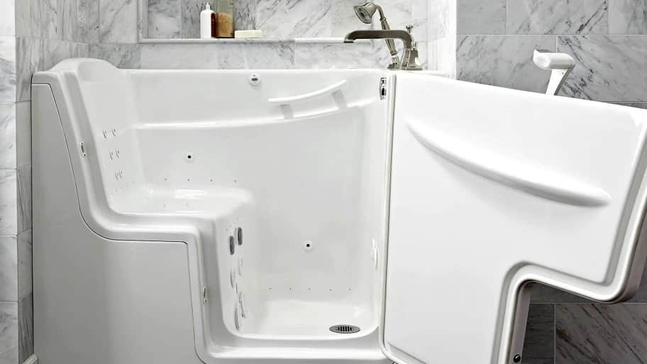 side view of walk-in tub with door open revealing bathtub with seat that slopes down to the drain (Photo by Photo courtesy of American Standard)