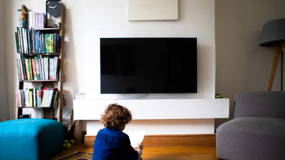 wall mounted tv in living room with small child sitting on ground