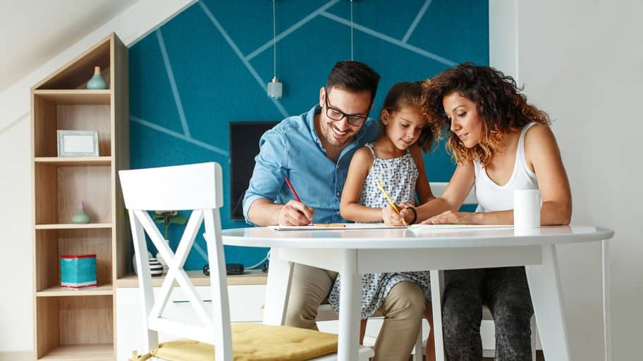 Family sitting at table coloring pictures  (Photo by BalanceFormCreative/Shutterstock.com)