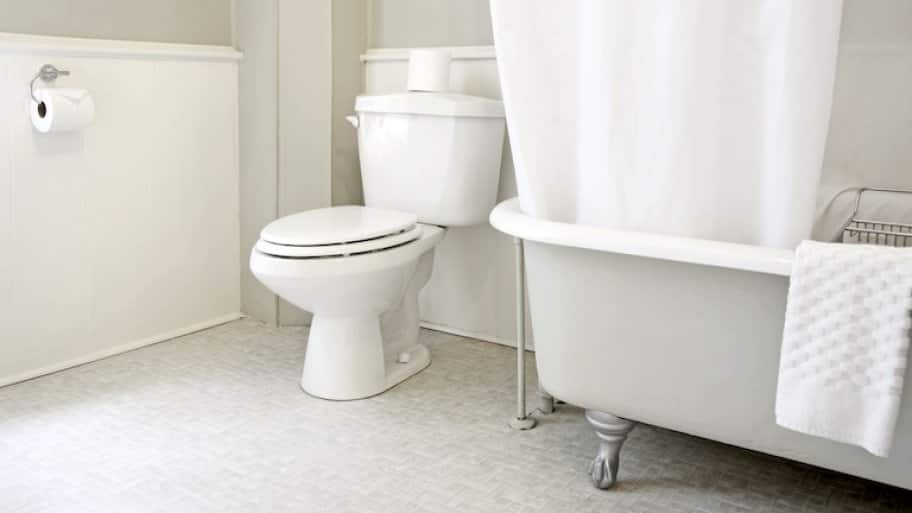 shot in white bathroom of white toilet and partial view of bathtub with white accents
