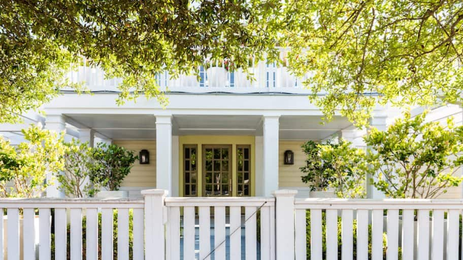 white wooden gate in front of white two-story house