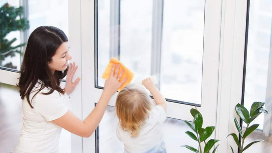 Mother and child cleaning window together