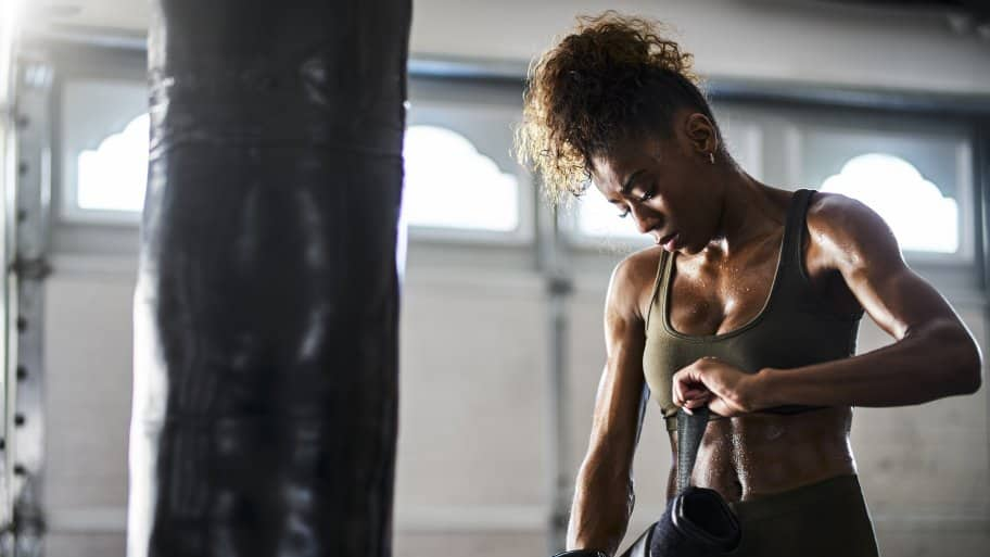Woman in gym clothes putting on boxing clothes while standing next to her punching bag in her garage home gym