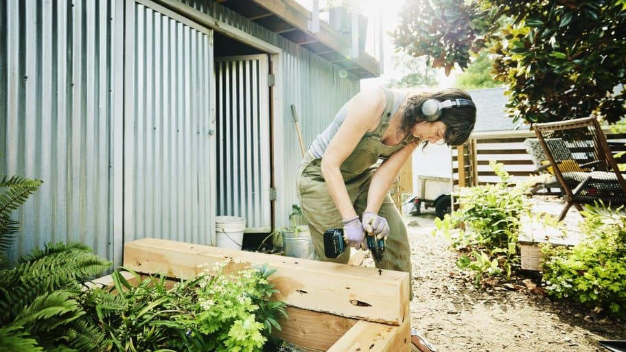 Woman building raised garden beds in backyard on summer afternoon