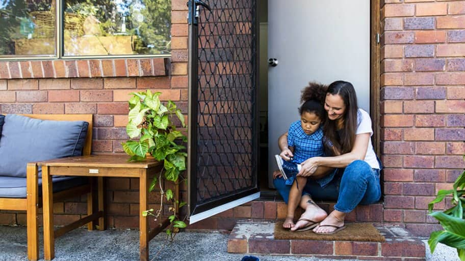 Woman helping child put on shoes with an open screen door (Photo by LOUISE BEAUMONT/ Moment via Getty Images)