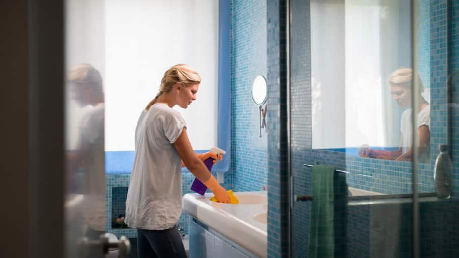 Woman cleaning her blue bathroom