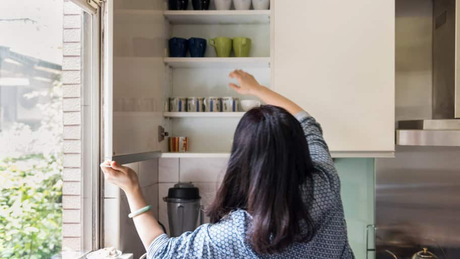A woman grabbing a cup from a kitchen cabinet