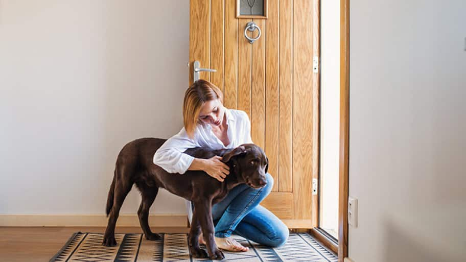 Woman pets dog by front door