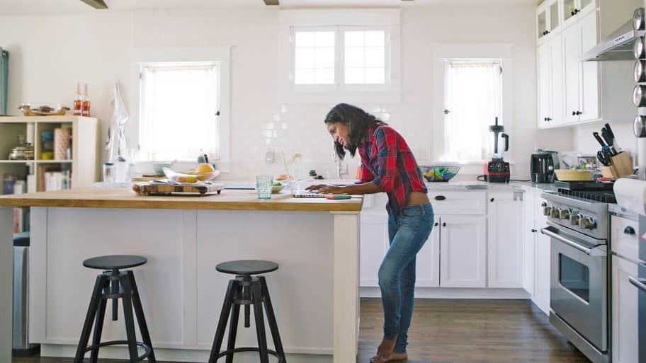Woman on laptop at kitchen island