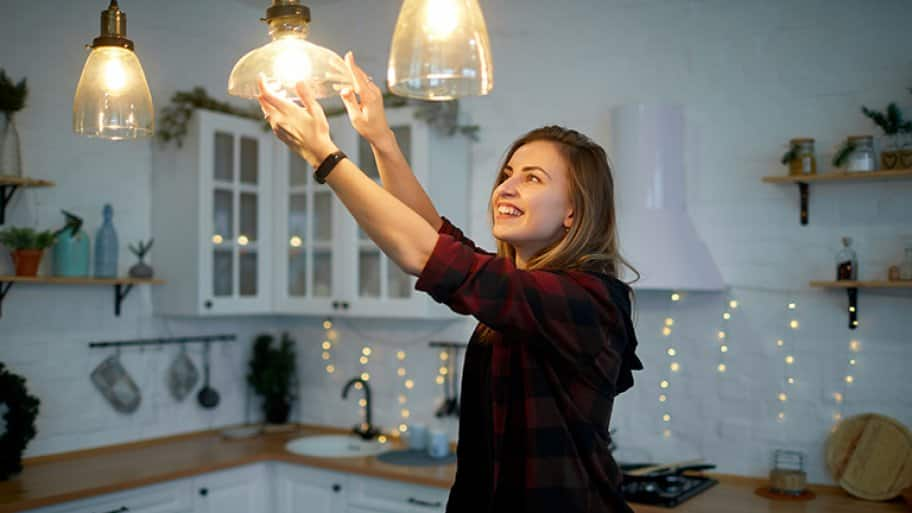 Woman screws in bulb on hanging light (Photo by By ryzhenko23 - stock.adobe.com)