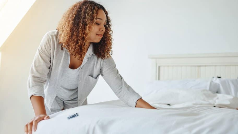 woman making white clean bed