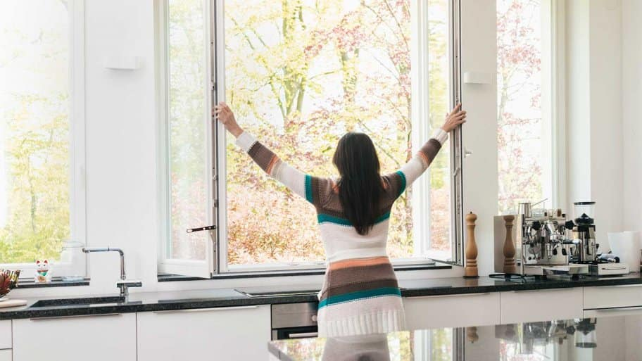Young woman in kitchen opening big window