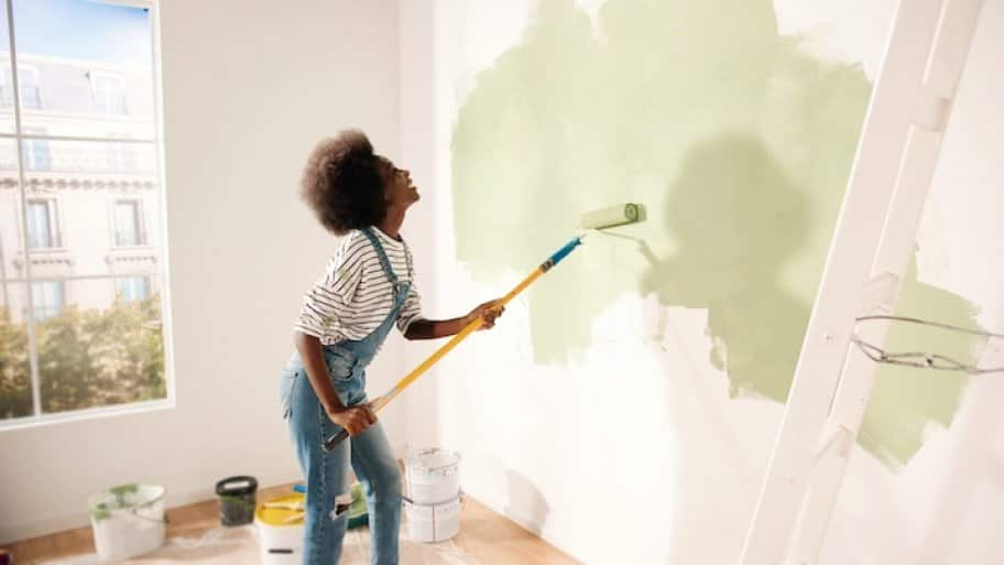 a woman in overalls painting a white wall with green paint and smiling