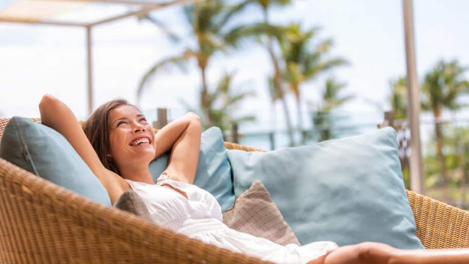 Women lounging in outdoor rattan chair with blue pillows