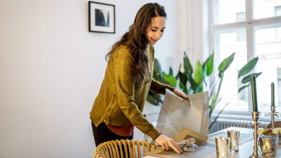 A woman setting the table by placing placemats