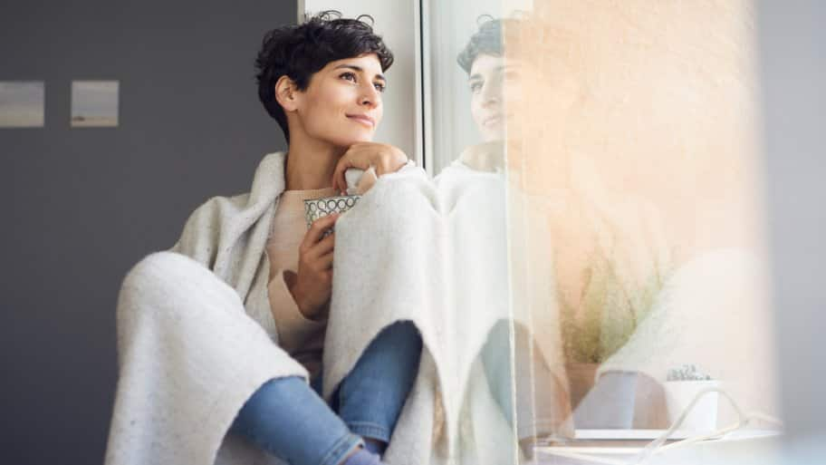 Woman covered in a blanket sitting by the window