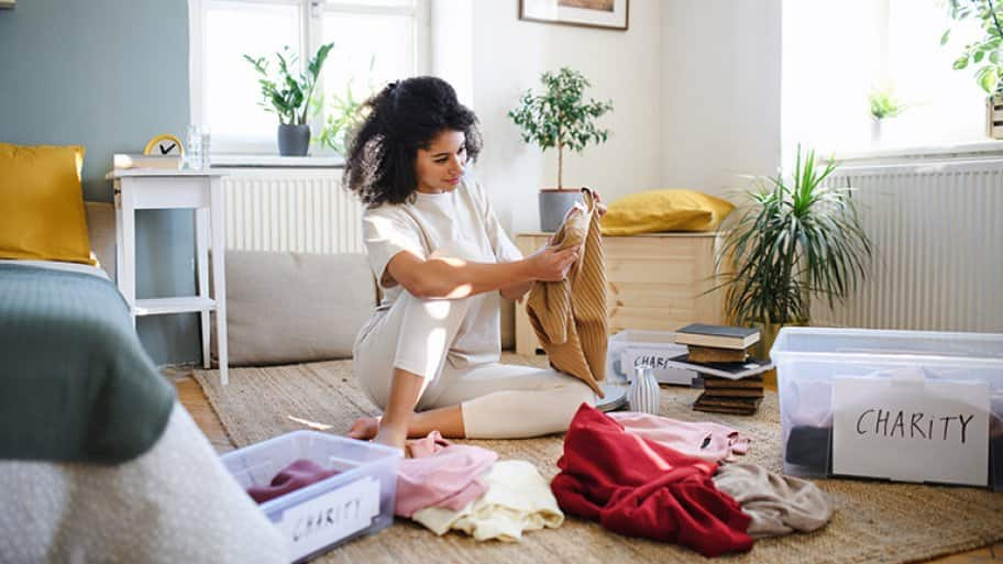 Young woman sorting her wardrobe clothes