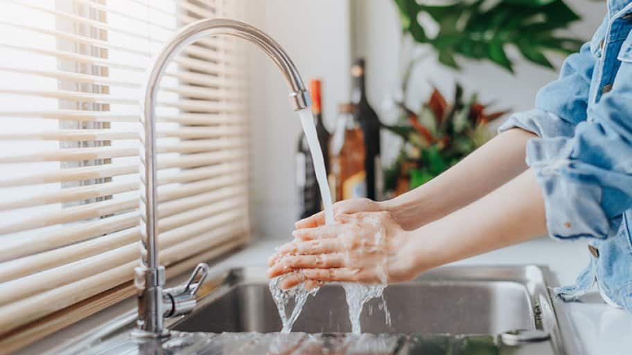 A woman washing her hands in kitchen sink