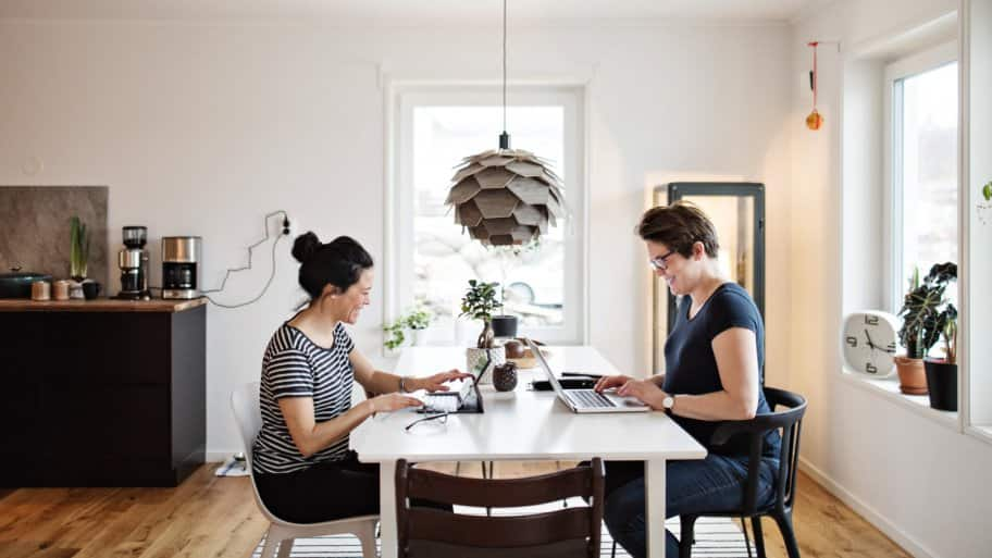 Two women working on their laptop at their living room table