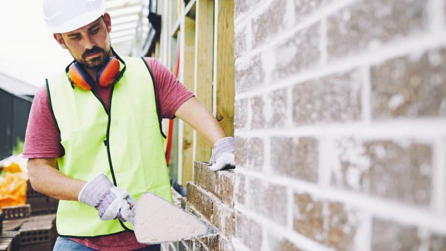 A worker checking on a brick wall of a construction site