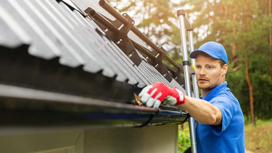 A worker cleans a house's gutter from leaves and dirt