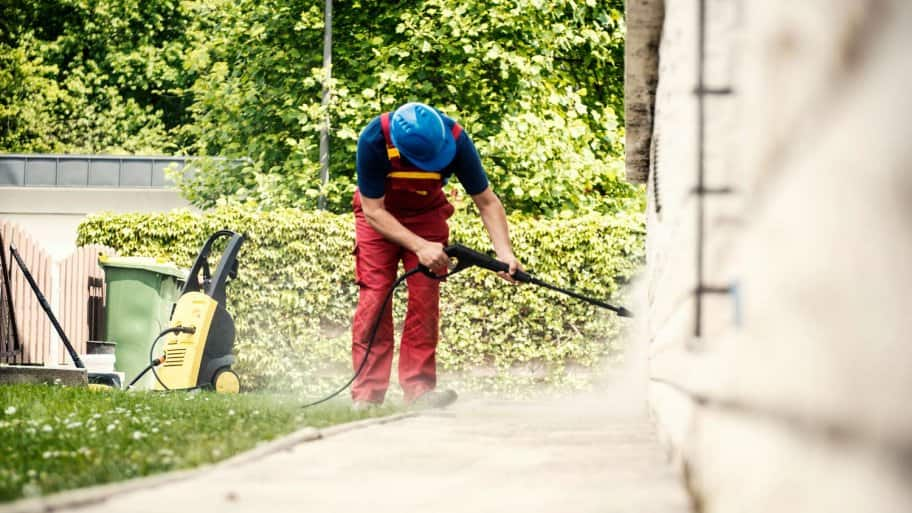 A worker cleaning the exterior of a house with a pressure washer