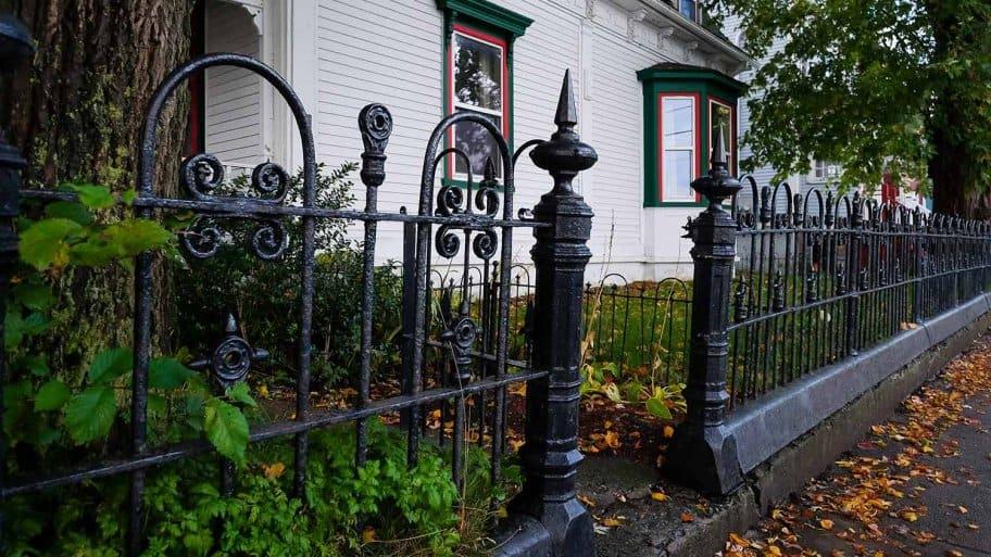 Wrought iron fence surrounding white house