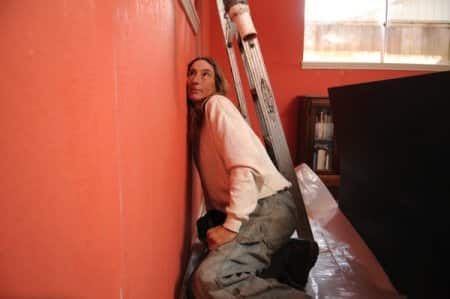 Jennifer Scott starts her job by listening to the bees in the wall. (Photo by Chris Curry)