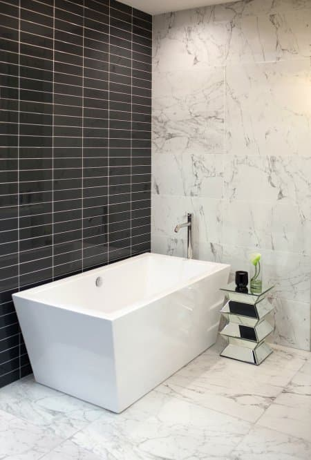 black tile with marble and soaker tub in bathroom