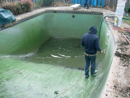 worker drains a pool to get it ready for a pool resurface