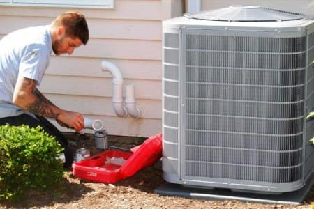 HVAC technician kneeling on ground while performing maintenance on a/c unit.