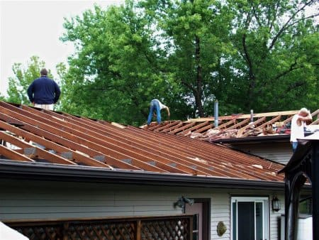 workers doing roof repair on a home