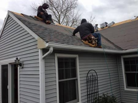 crew on roof replacing asphalt shingles during winter