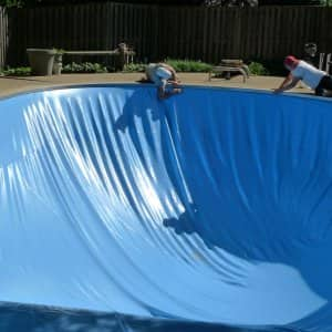 workmen replace a pool liner