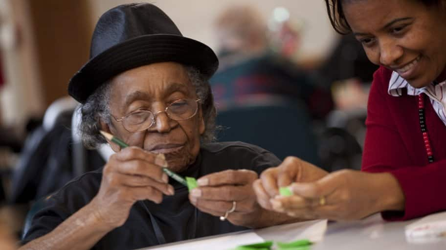 elderly woman using pencil and small piece of paper