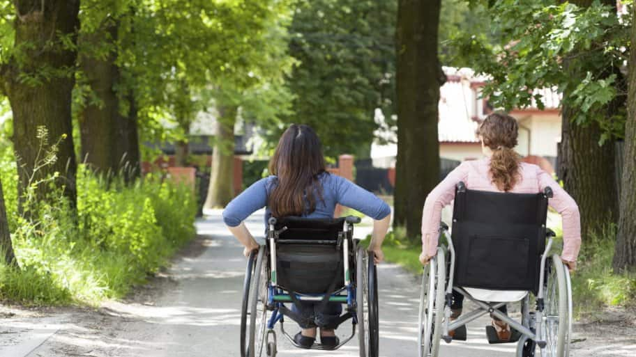 Two young girls in wheel chairs move along a path together.