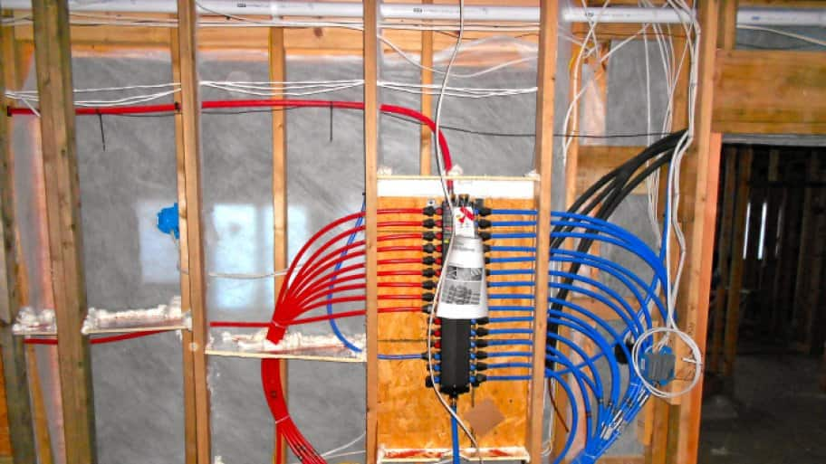 Red and blue PEX plumbing pipe installed in a wall under construction.