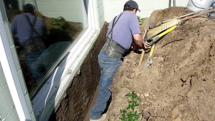basement waterproofing contractor working