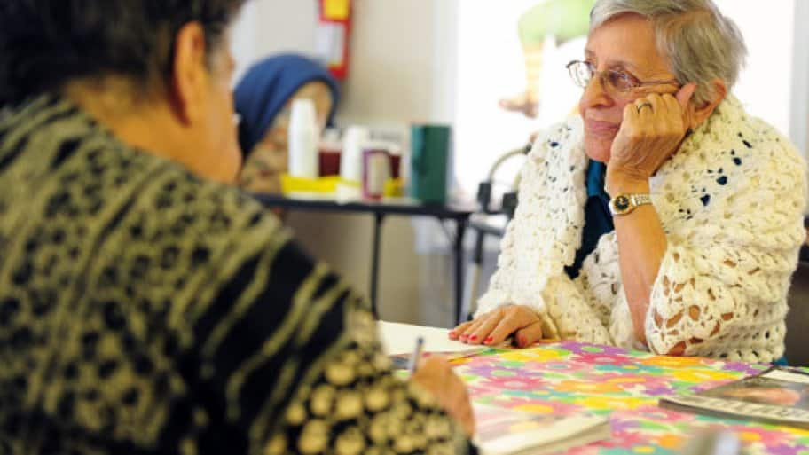 elderly woman sits at a table with a man who is writing.