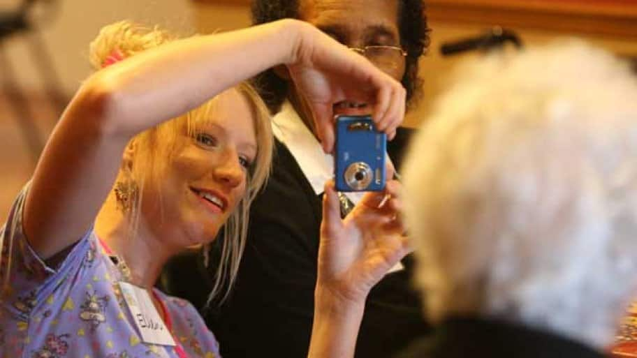 nursing home worker takes a photo of residents.